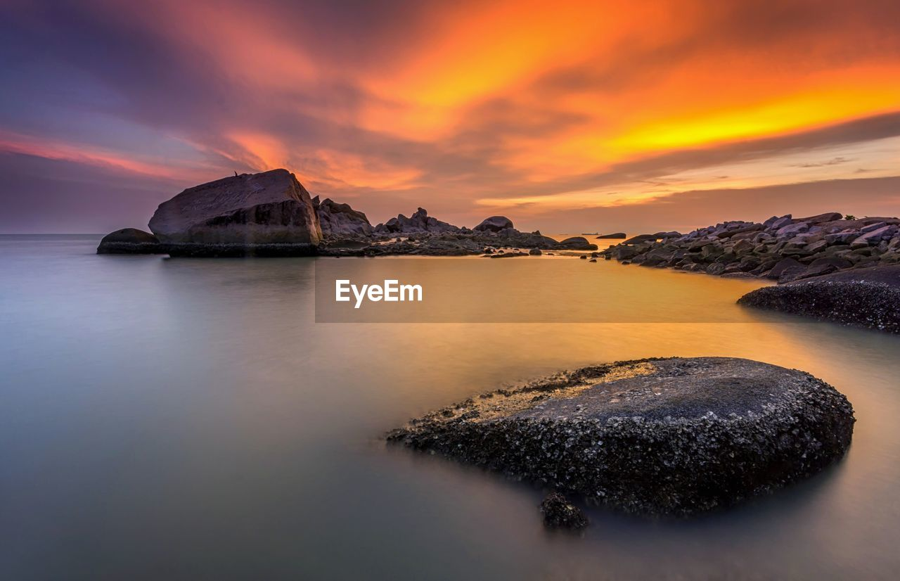 water, beauty in nature, scenics - nature, rock, sunset, solid, sky, rock - object, cloud - sky, tranquil scene, tranquility, sea, waterfront, nature, no people, idyllic, rock formation, orange color, long exposure, outdoors, stack rock