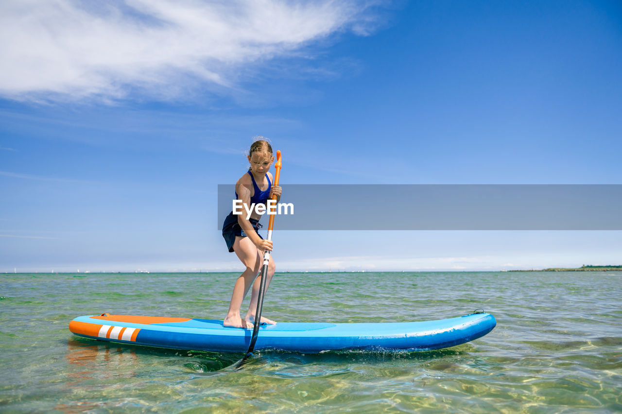 Man on boat in sea against blue sky