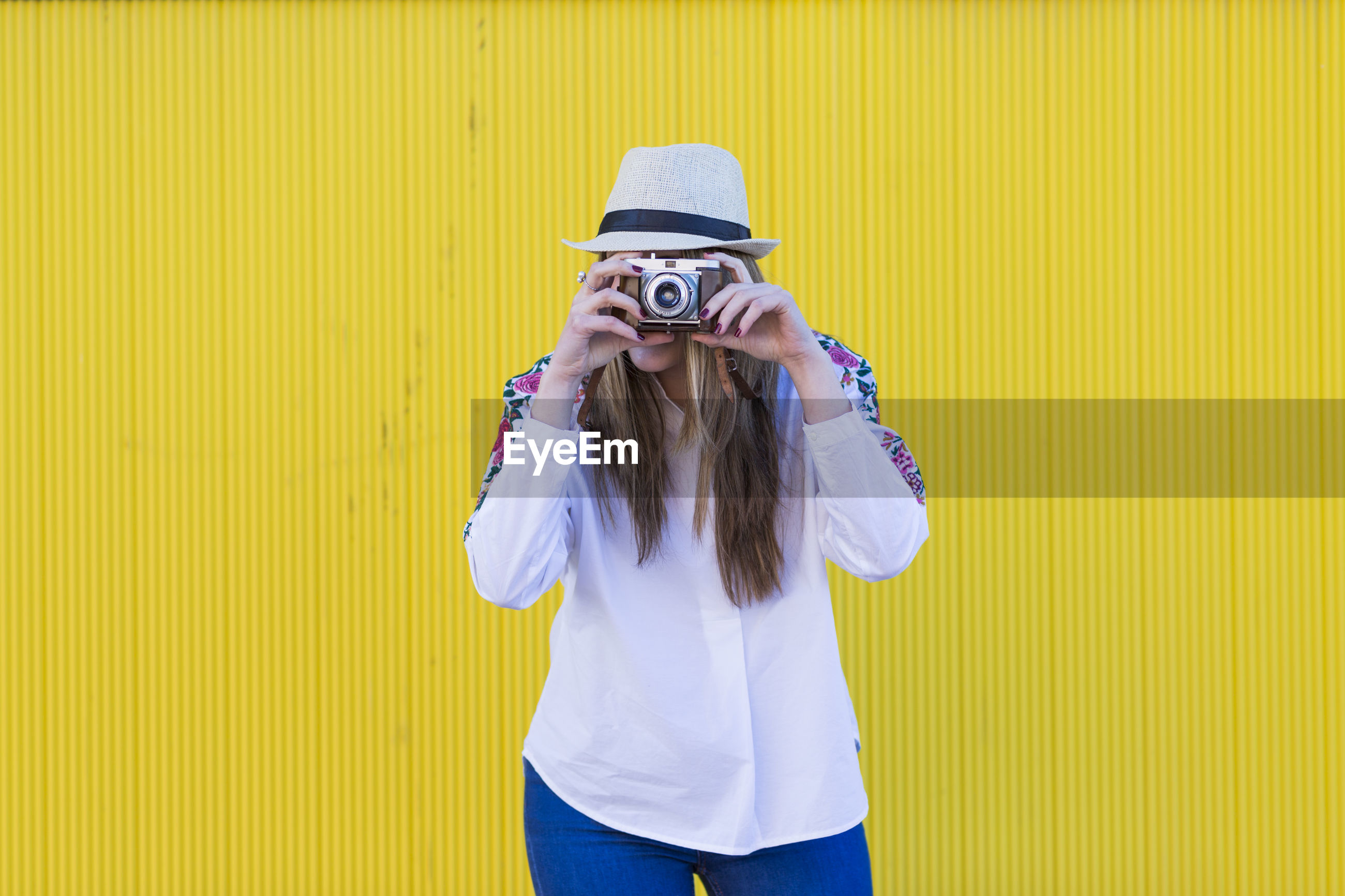 Portrait of woman photographing against yellow wall