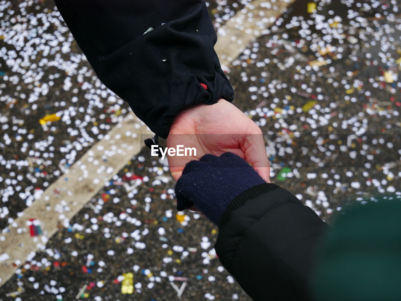 Cropped image of friends holding hands over confetti
