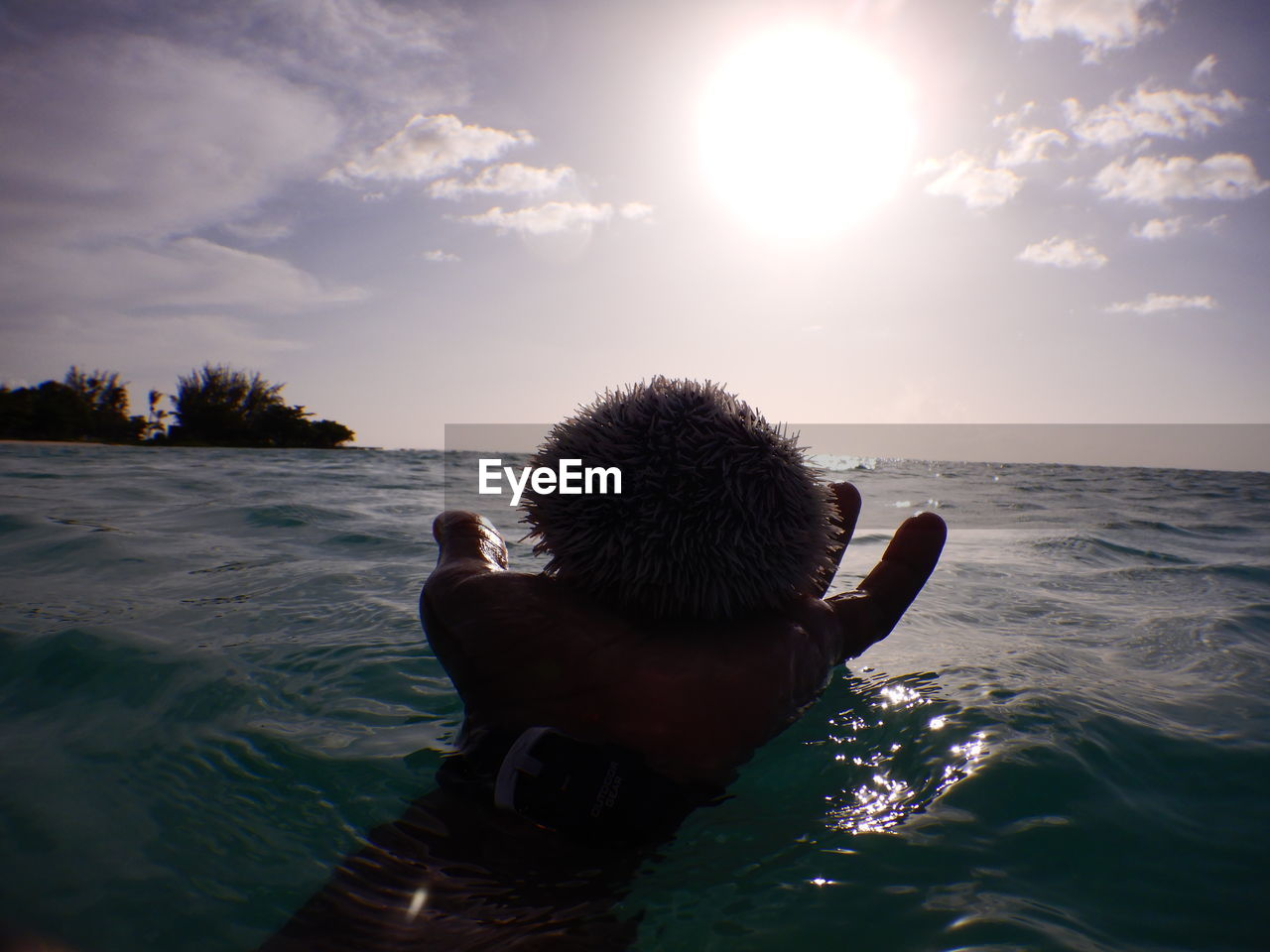 sky, sea, water, real people, lifestyles, leisure activity, hand, human hand, one person, nature, sunlight, beauty in nature, human body part, men, sun, scenics - nature, cloud - sky, unrecognizable person, body part, outdoors, horizon over water, finger, human arm