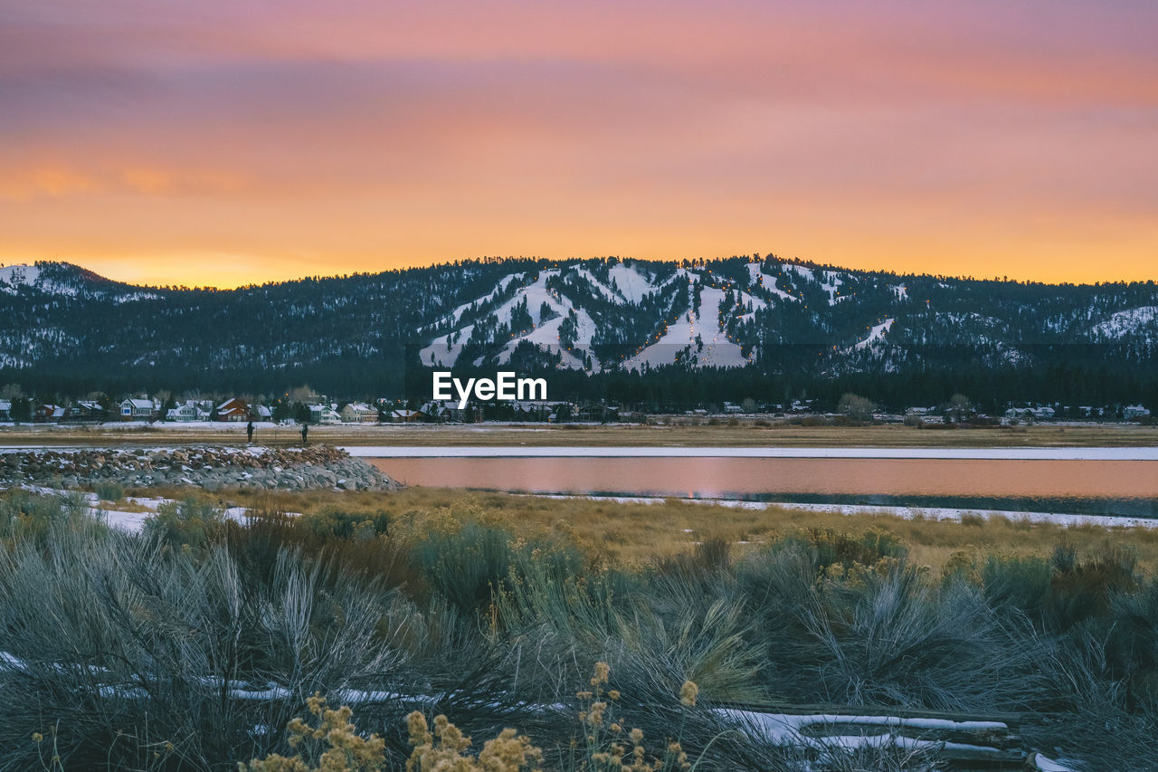 Scenic View Of Lake Amd Snowcapped Mountains Against Cloudy Sky During Sunset