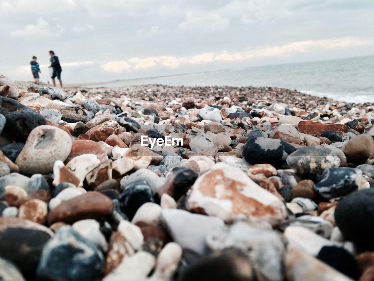 People Walking On Rocks At Beach Against Sky