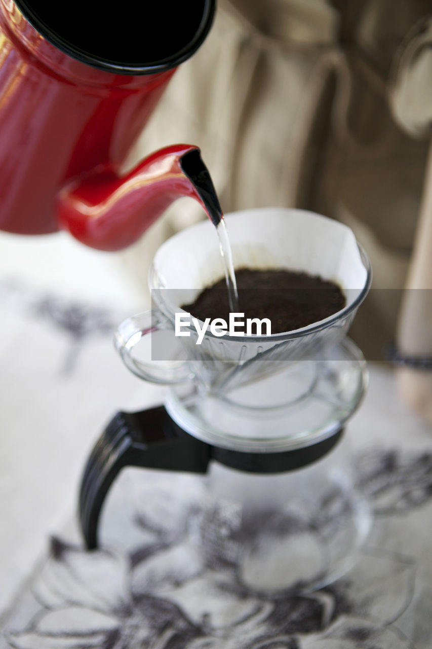 Close-Up Of Jug Pouring Water In Coffee Cup At Table