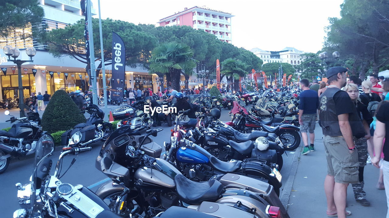 land vehicle, mode of transport, transportation, motorcycle, street, bicycle, stationary, real people, men, outdoors, city, built structure, road, architecture, riding, cycling, building exterior, scooter, helmet, tree, biker, day, sky, people
