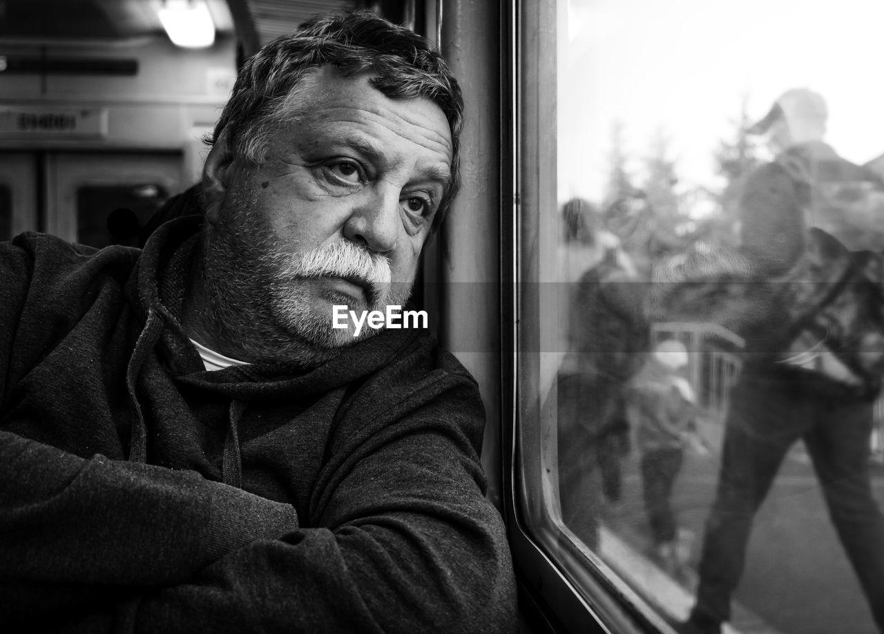 Senior Man Looking Through Train Window