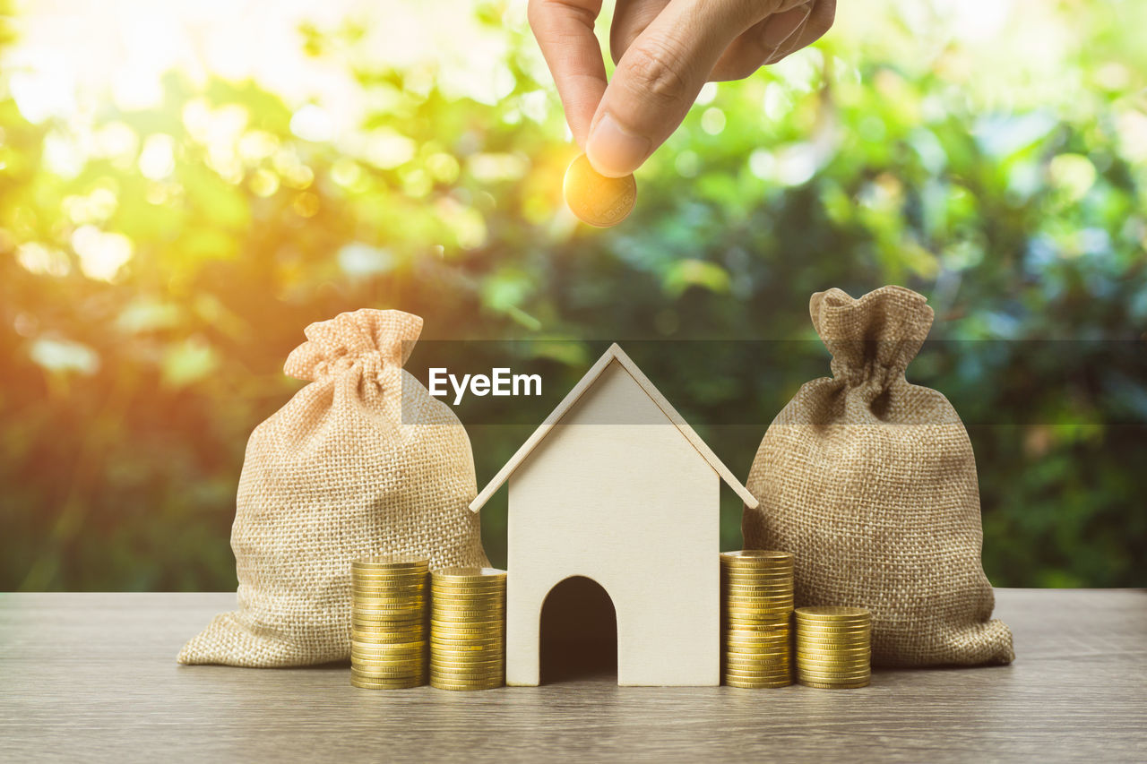 Cropped hand of person holding coin over model home by sacks and stack on table