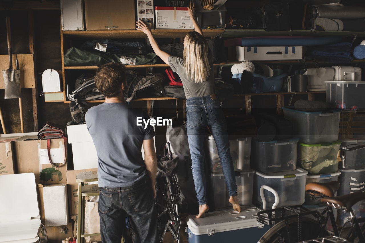 Man looking at woman while she adjusting boxes at home