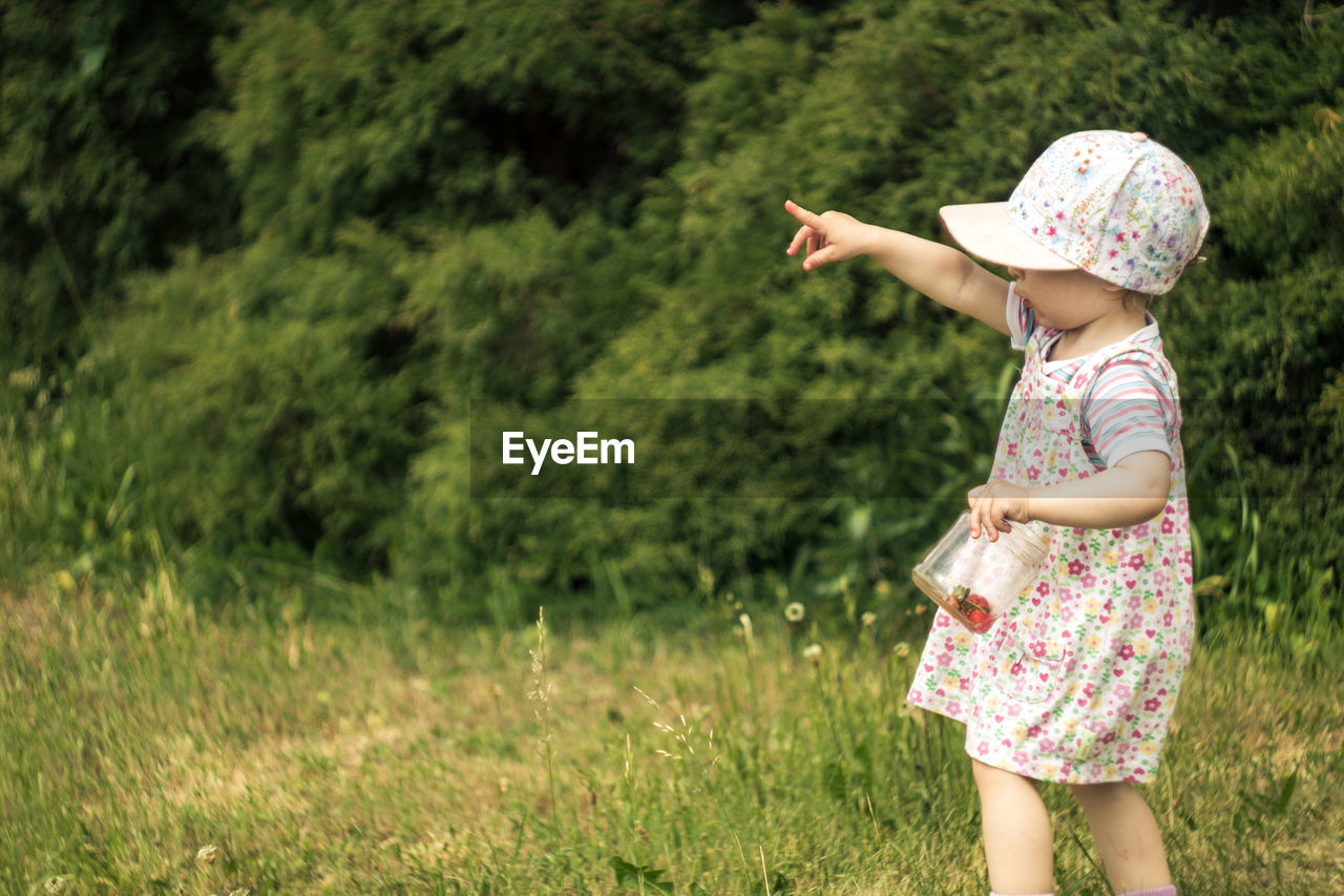 Girl Standing On Grass Against Trees