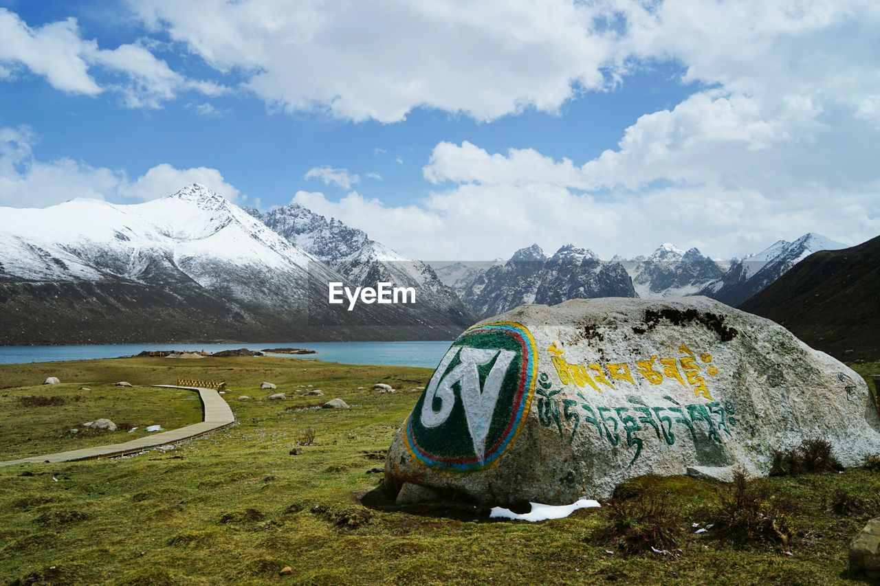 Text Written On Rock Against Snowcapped Mountains