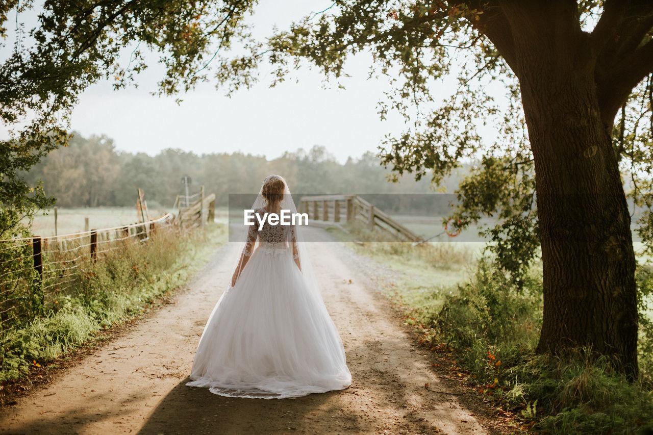 Rear View Of Bride Walking On Footpath
