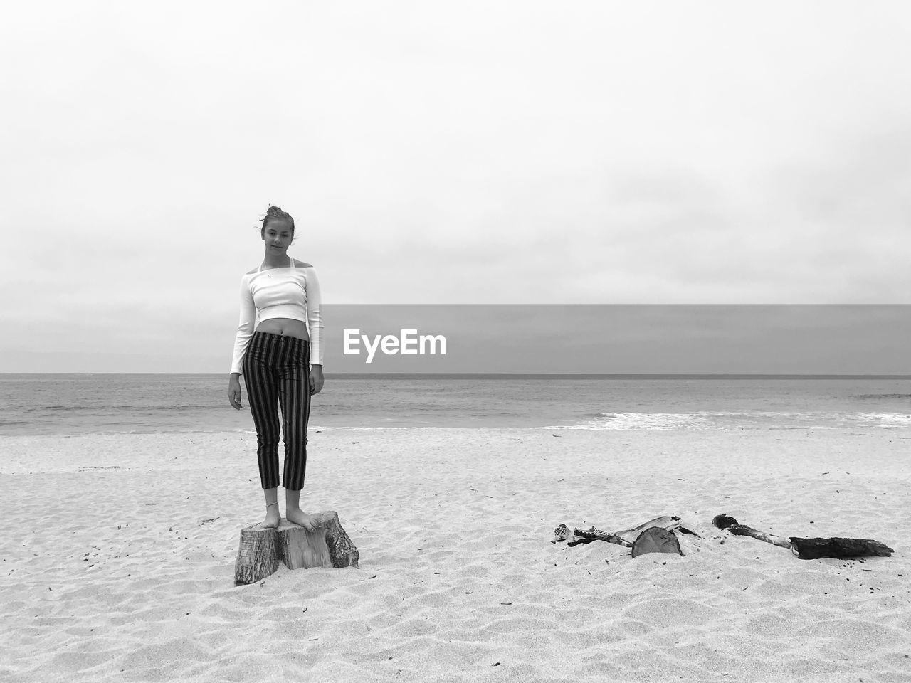Girl standing on beach against sky