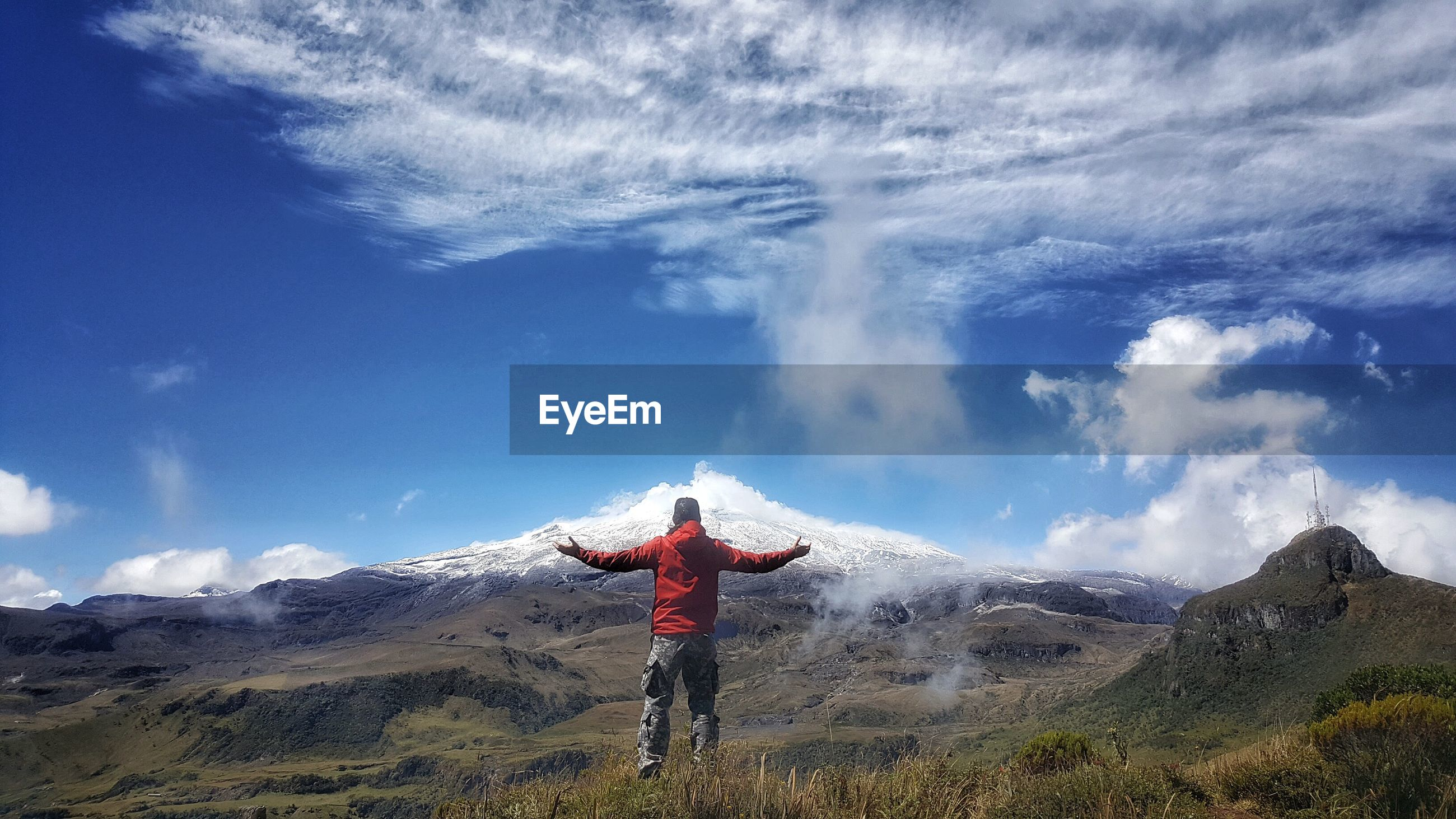 Rear view of man with arms outstretched standing on landscape against sky