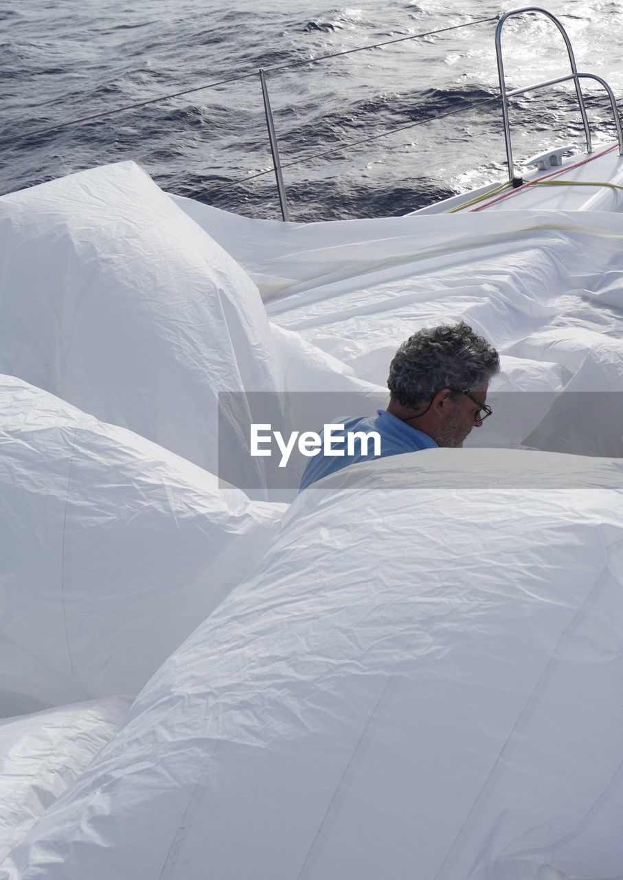MAN LYING ON SNOW COVERED BED