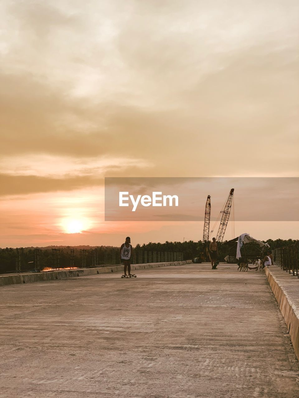 sky, sunset, cloud - sky, real people, nature, architecture, industry, men, built structure, construction industry, orange color, outdoors, people, machinery, lifestyles, incidental people, transportation, road, construction site, full length