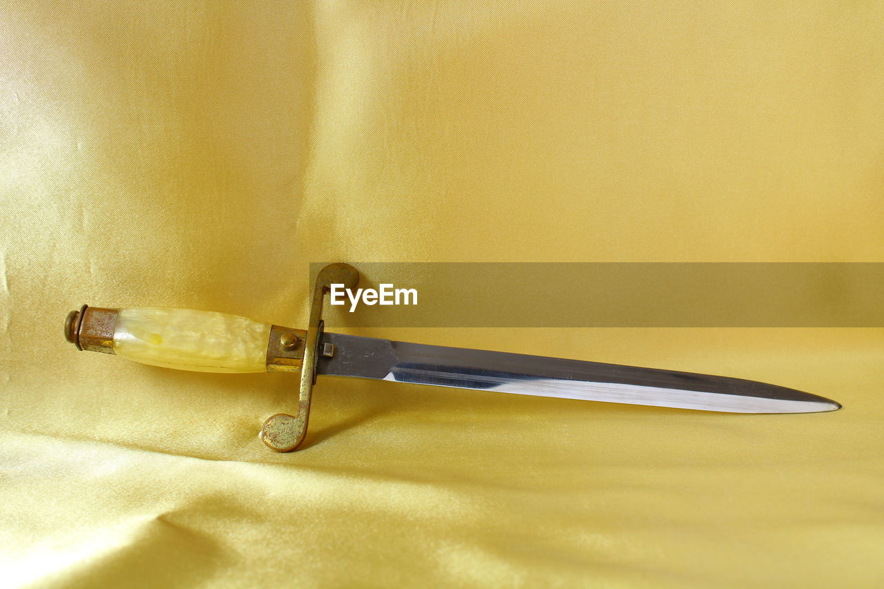yellow, still life, no people, close-up, fork, single object, gold colored, table, indoors, studio shot, silver, day