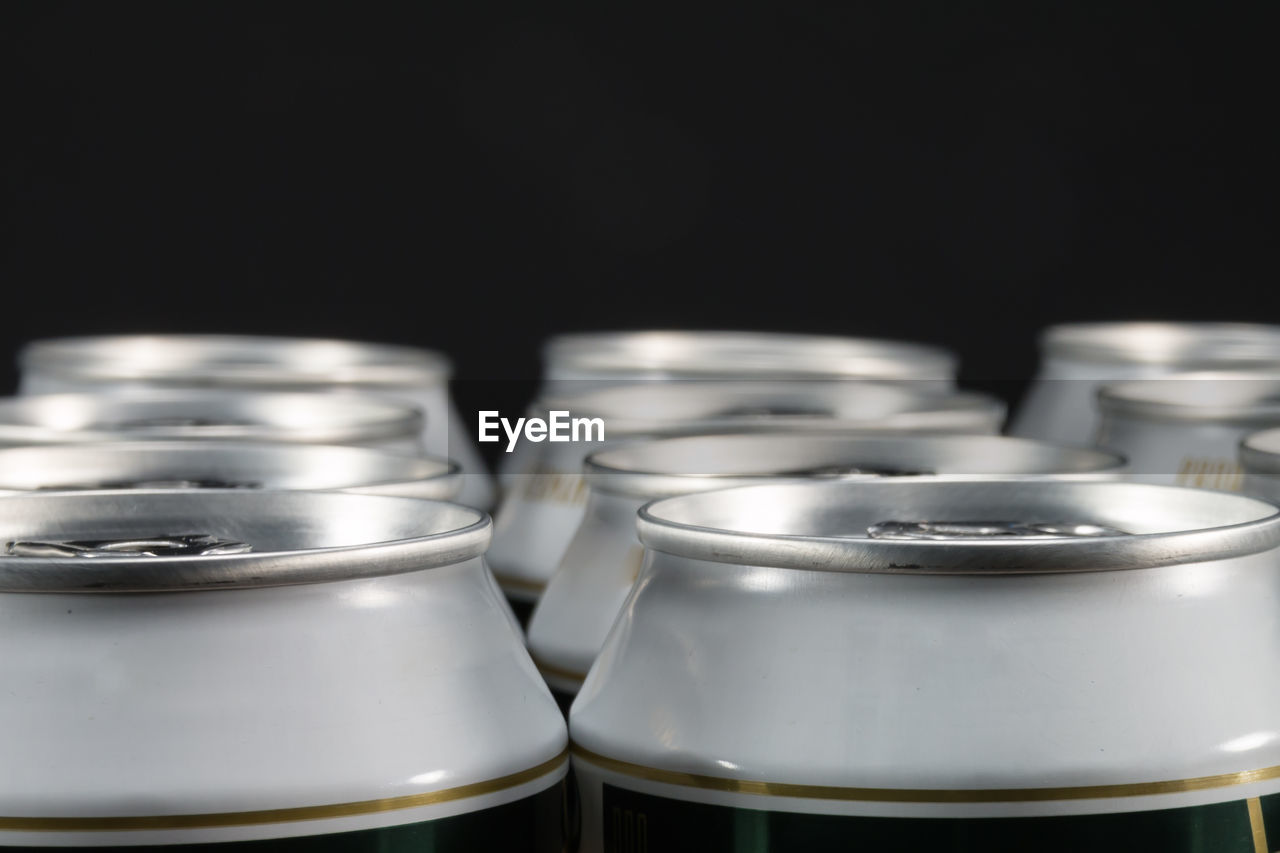 Close-up of drink cans against black background