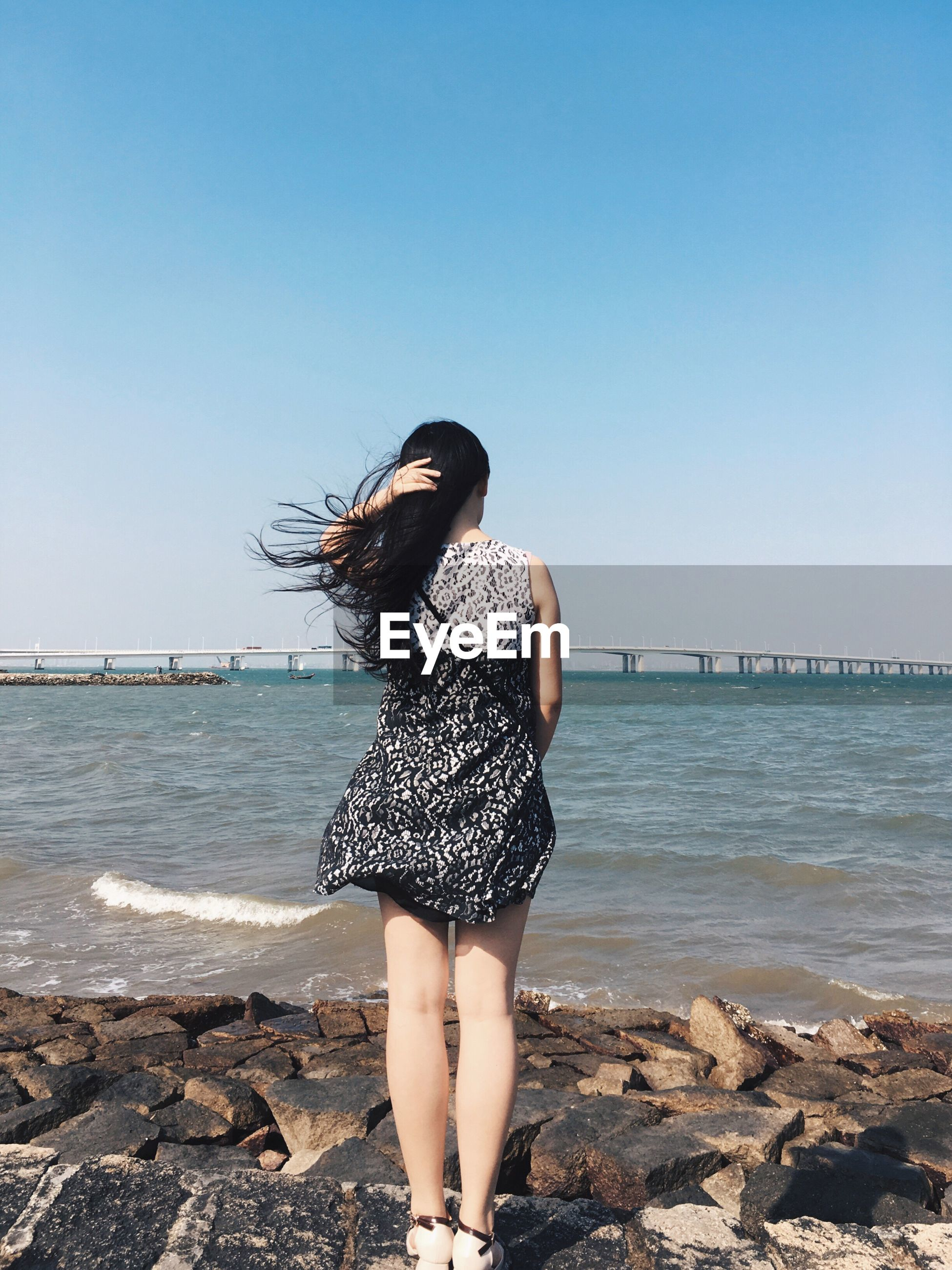 sea, water, clear sky, one person, leisure activity, real people, nature, horizon over water, lifestyles, outdoors, rock - object, standing, young women, long hair, day, young adult, beauty in nature, beach, full length, scenics, sky, beautiful woman