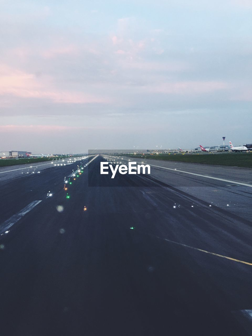 High angle view of illuminated airport runway against cloudy sky during sunset