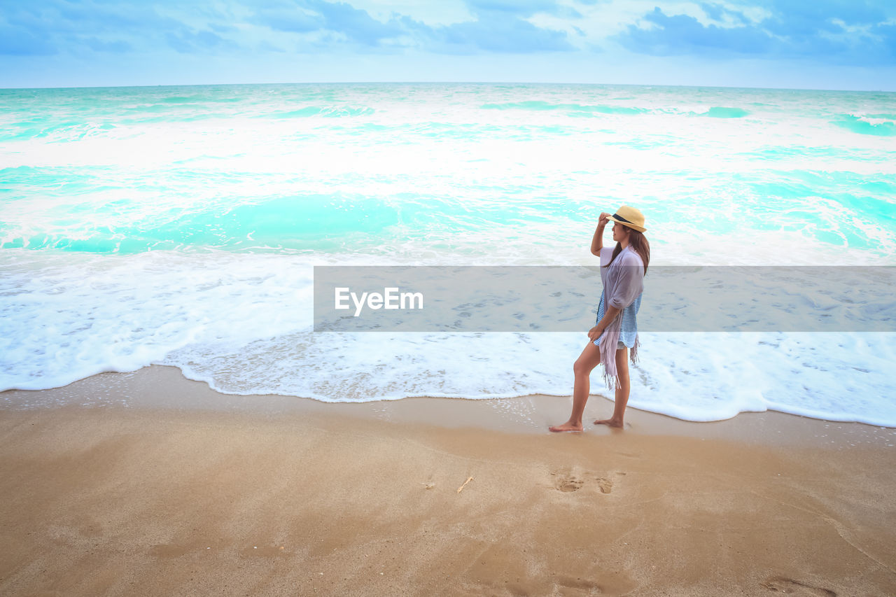 sea, beach, water, land, one person, leisure activity, lifestyles, real people, full length, beauty in nature, sky, motion, standing, scenics - nature, nature, horizon, women, wave, horizon over water, beautiful woman, outdoors