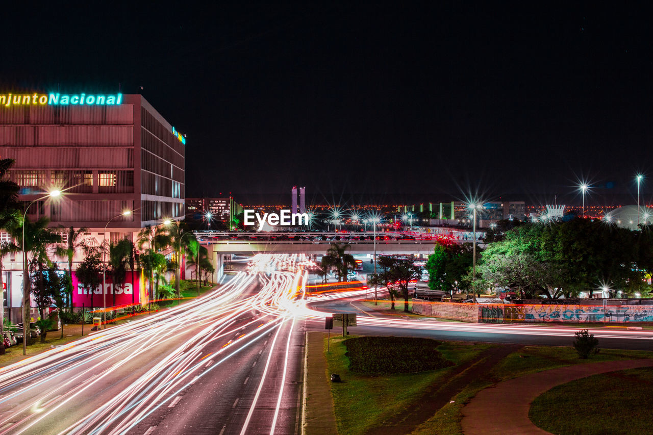 illuminated, night, building exterior, long exposure, city, architecture, built structure, motion, street, light trail, road, speed, transportation, city life, sky, blurred motion, building, city street, no people, nature, cityscape, outdoors, office building exterior