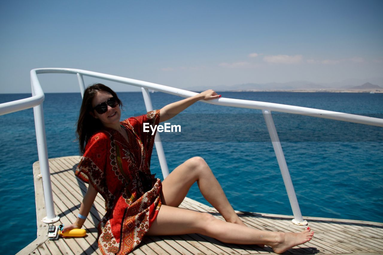 Young Woman Sitting On Boat Sailing In Sea Against Sky