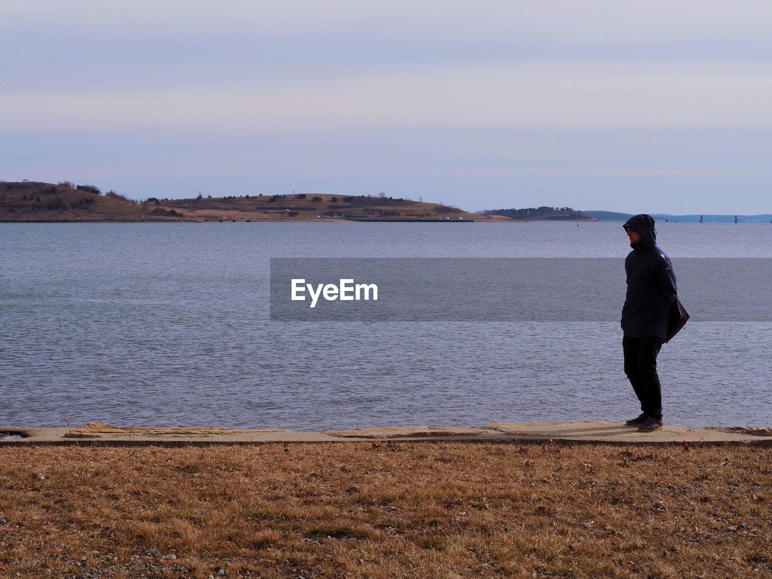 Full length of man standing at lakeshore against sky