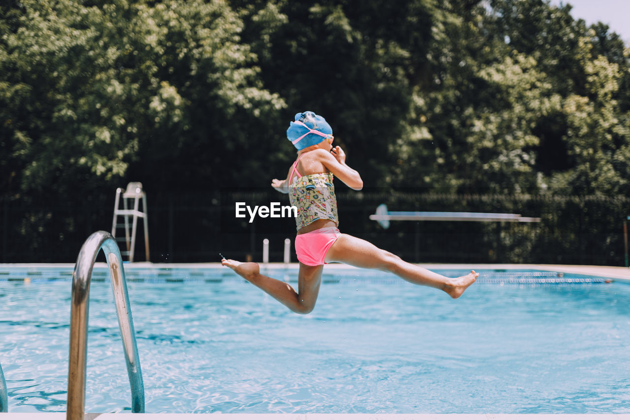 Side View Of Girl Diving Into Swimming Pool