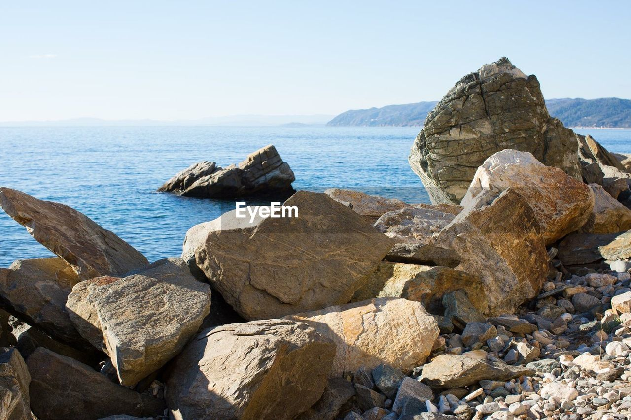 ROCKS ON SHORE AGAINST CLEAR SKY