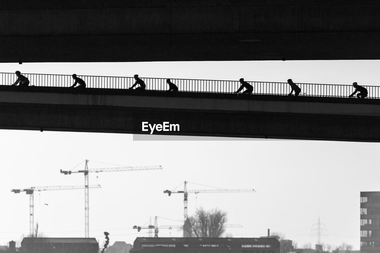 Silhouette People Cycling On Bridge Against Clear Sky