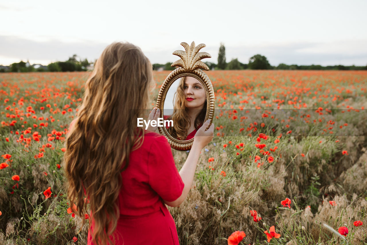 Beautiful young woman by poppy flowers on field looking at her reflection