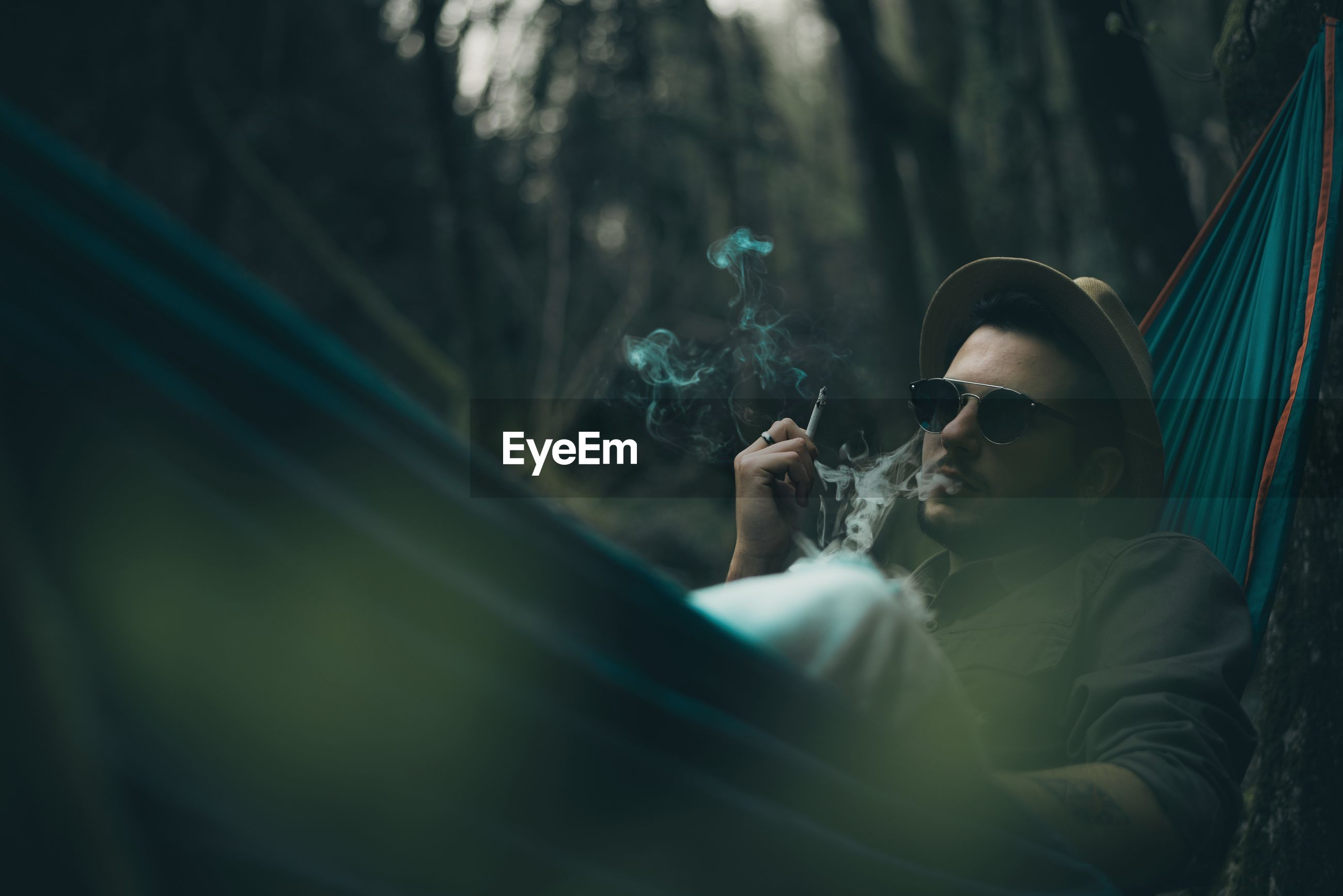 Man smoking cigarette while lying on hammock in forest