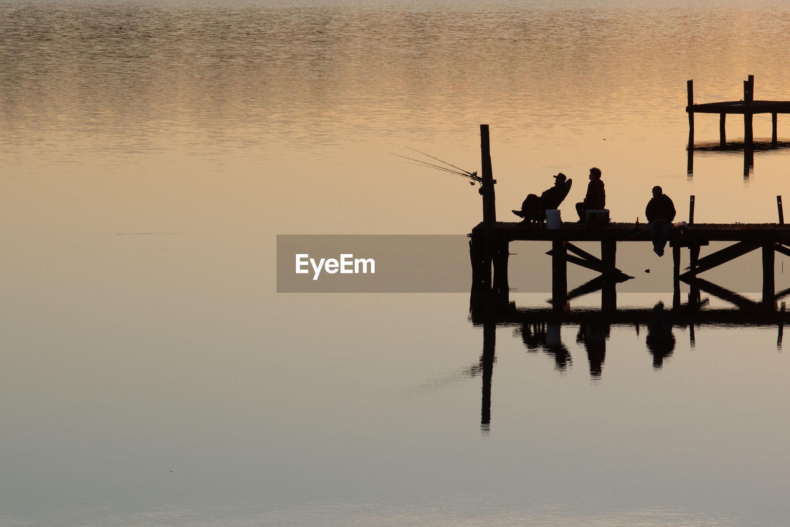 SILHOUETTE MEN STANDING ON LAKE AGAINST SKY DURING SUNSET