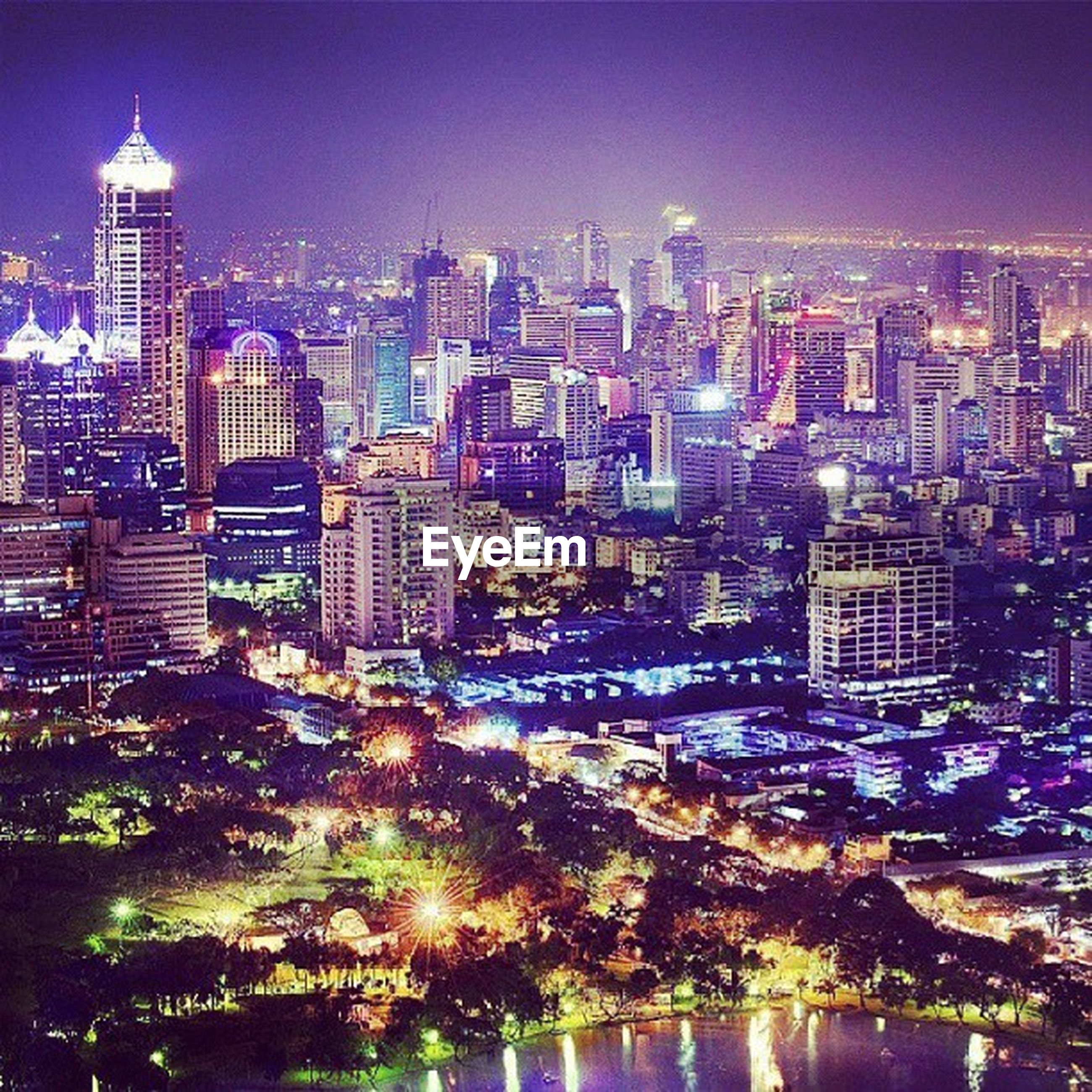 city, building exterior, illuminated, cityscape, architecture, skyscraper, built structure, night, modern, tall - high, office building, urban skyline, tower, water, crowded, financial district, city life, high angle view, residential district, river