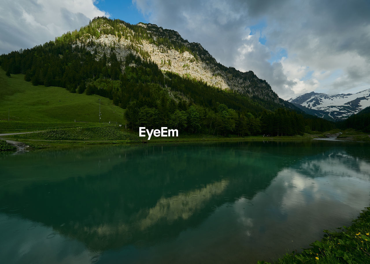 mountain, scenics - nature, water, beauty in nature, cloud - sky, tranquil scene, lake, sky, tranquility, reflection, non-urban scene, idyllic, green color, nature, mountain range, plant, day, no people, waterfront, snowcapped mountain, mountain peak, reflection lake