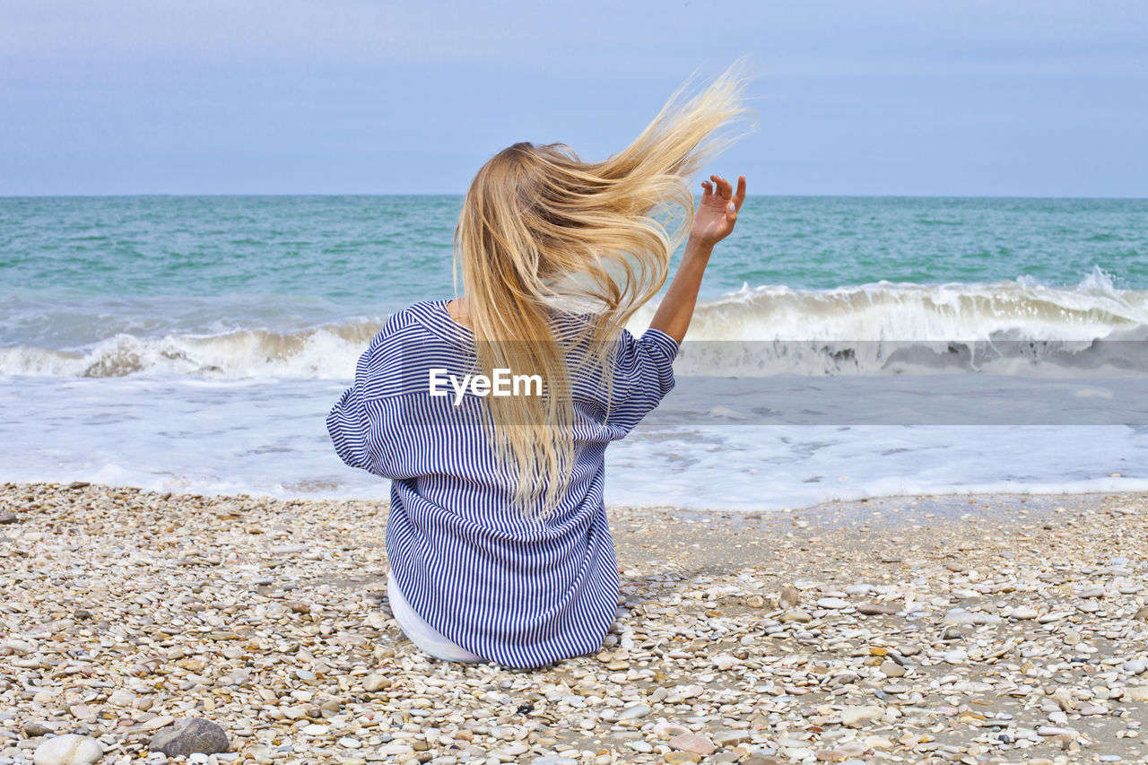 sea, land, beach, one person, hair, water, hairstyle, long hair, leisure activity, blond hair, real people, horizon over water, beauty in nature, rear view, women, horizon, lifestyles, motion, scenics - nature, tousled hair, wind, outdoors