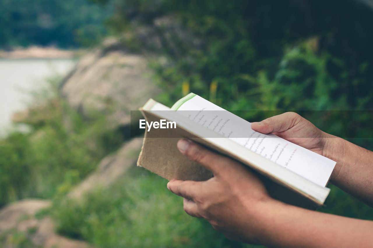 CROPPED IMAGE OF PERSON HOLDING BOOK WITH TEXT