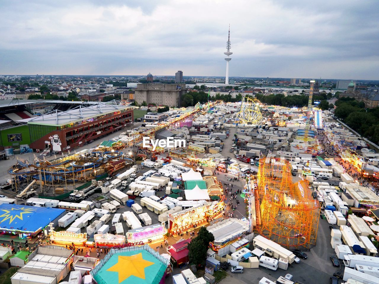 Funfair By Heinrich-Hertz-Turm In City Against Cloudy Sky