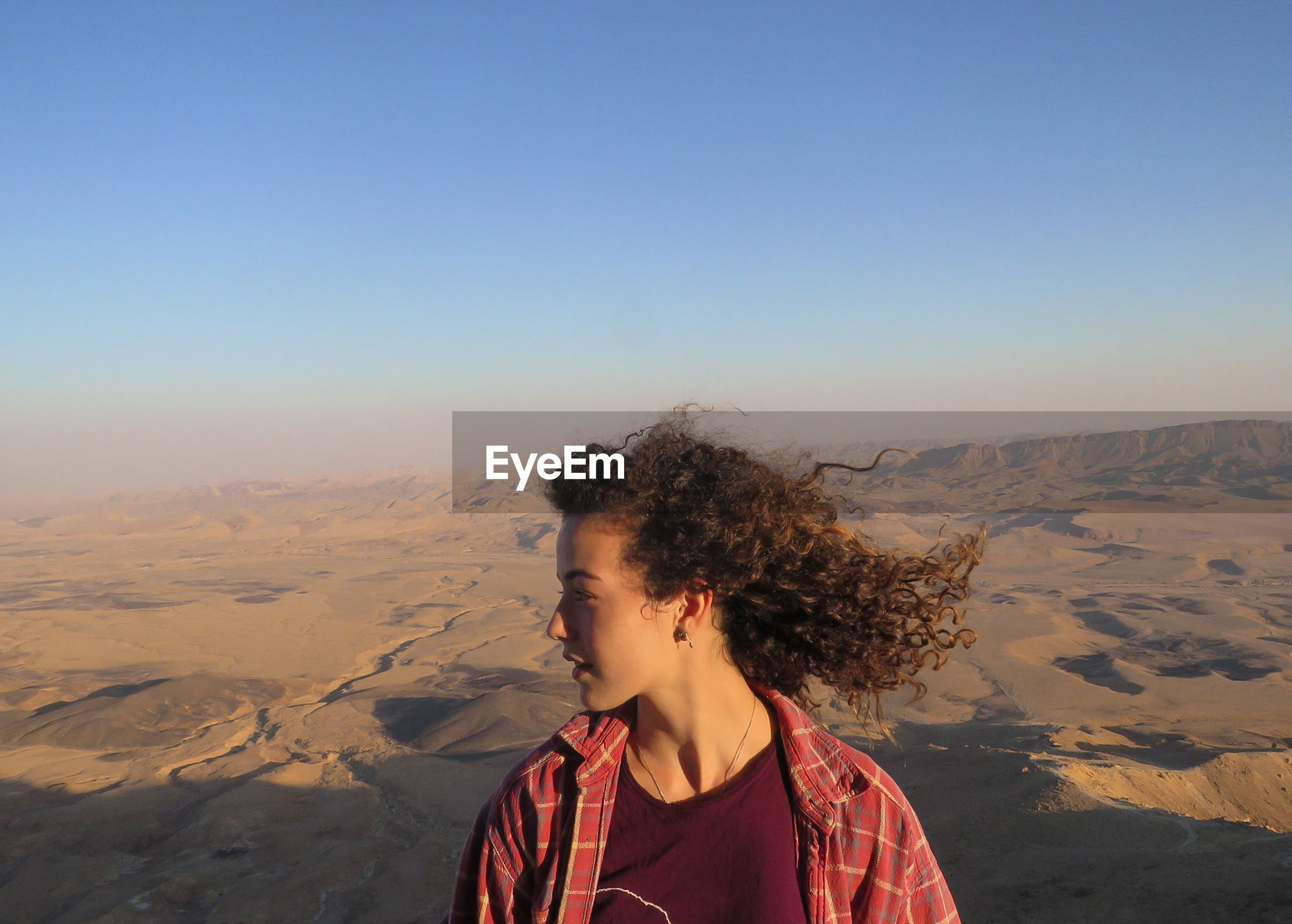 Young woman looking at landscape against clear blue sky