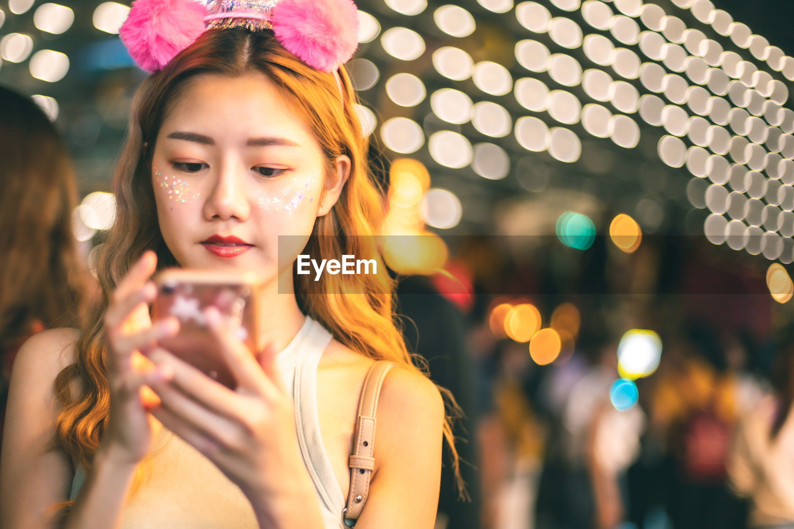 Young woman using mobile against illuminated lights