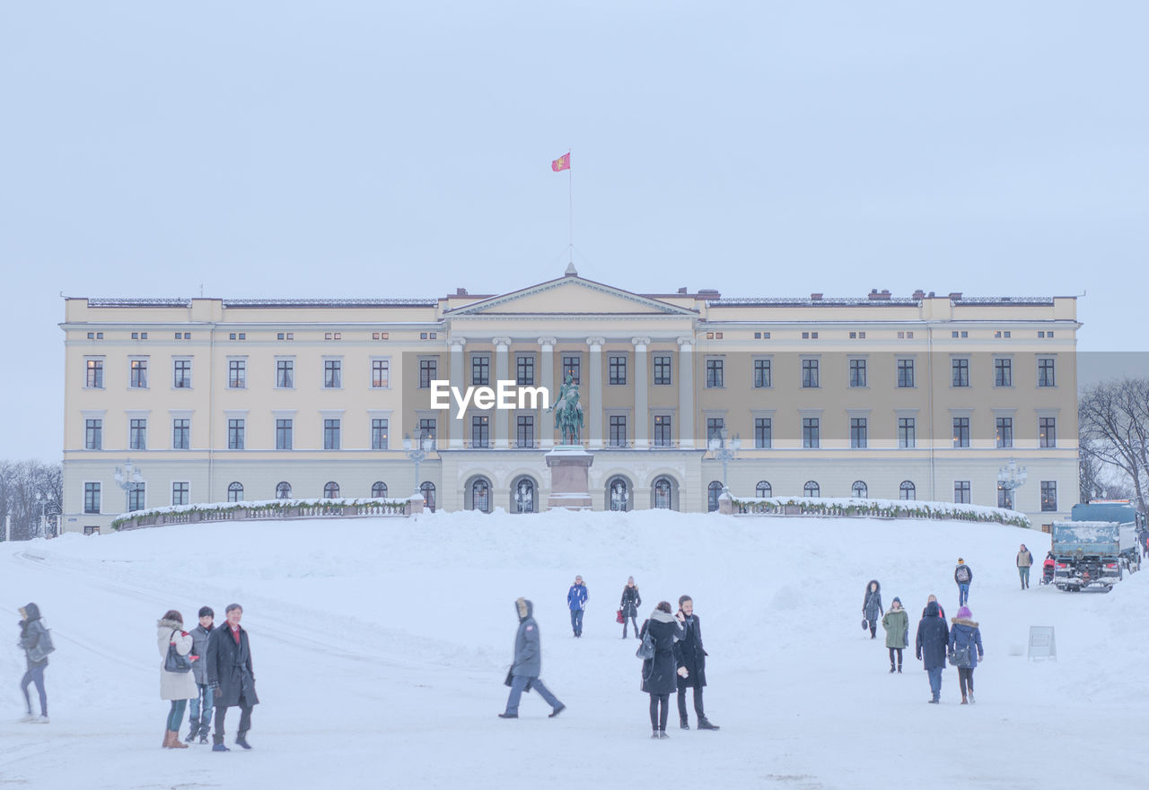People outside royal palace against sky during winter