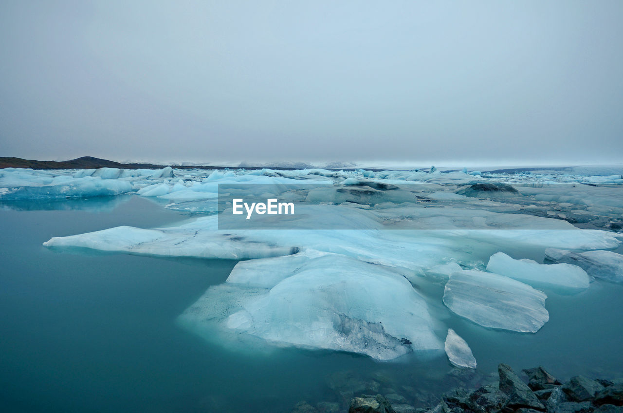 water, ice, cold temperature, sky, frozen, sea, beauty in nature, scenics - nature, glacier, winter, nature, tranquil scene, tranquility, environment, iceberg - ice formation, day, no people, snow, iceberg, outdoors, horizon over water, floating on water, melting
