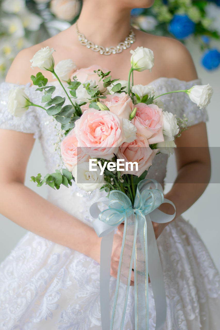wedding, celebration, newlywed, bride, event, flower, bouquet, flower arrangement, flowering plant, wedding dress, life events, plant, women, adult, one person, holding, rose, rose - flower, real people, midsection, hand, wedding ceremony, flower head