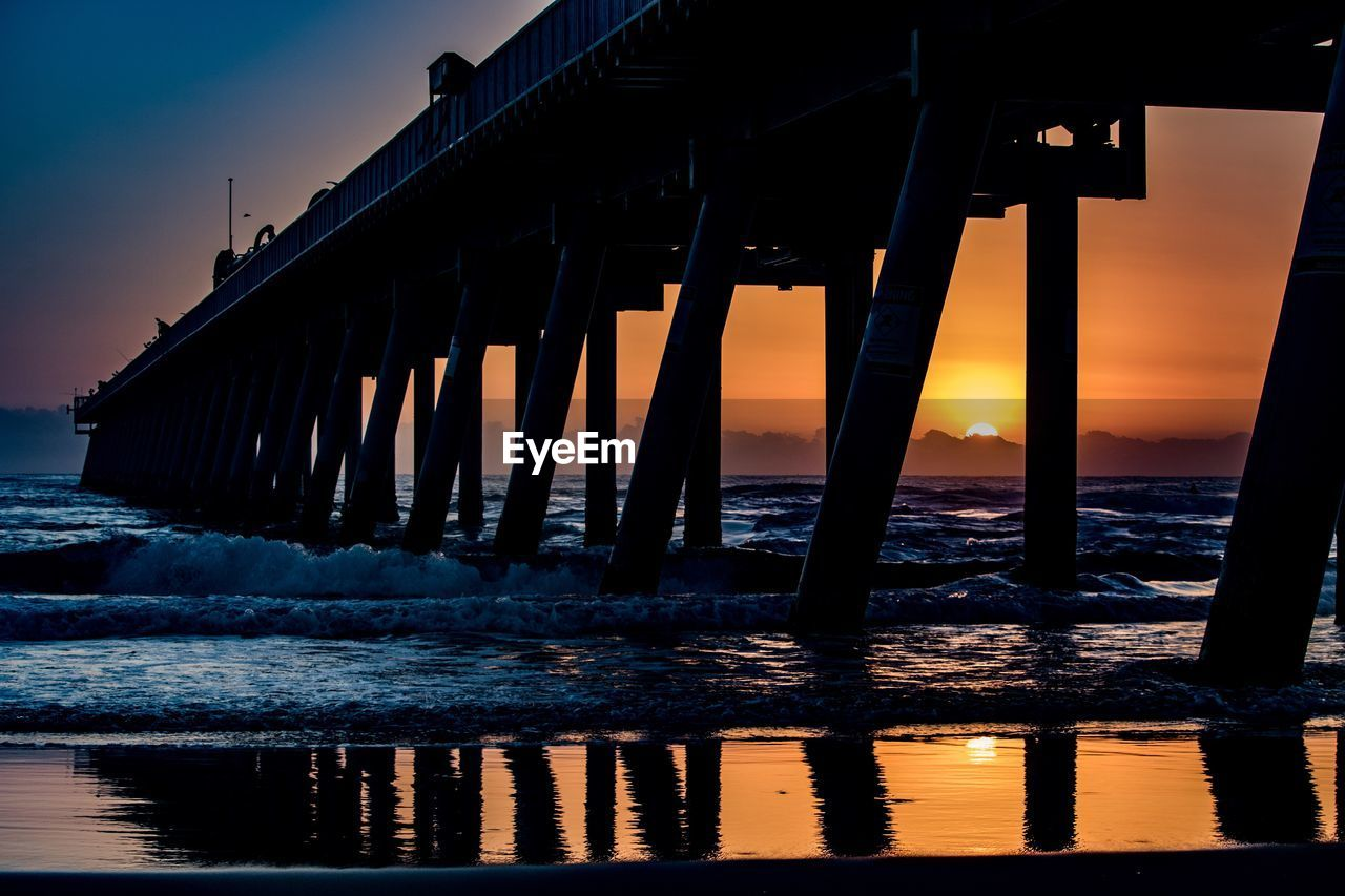 water, sunset, sky, sea, architecture, built structure, pier, nature, scenics - nature, connection, beauty in nature, tranquility, horizon, reflection, orange color, horizon over water, no people, tranquil scene, waterfront, architectural column, underneath, wooden post