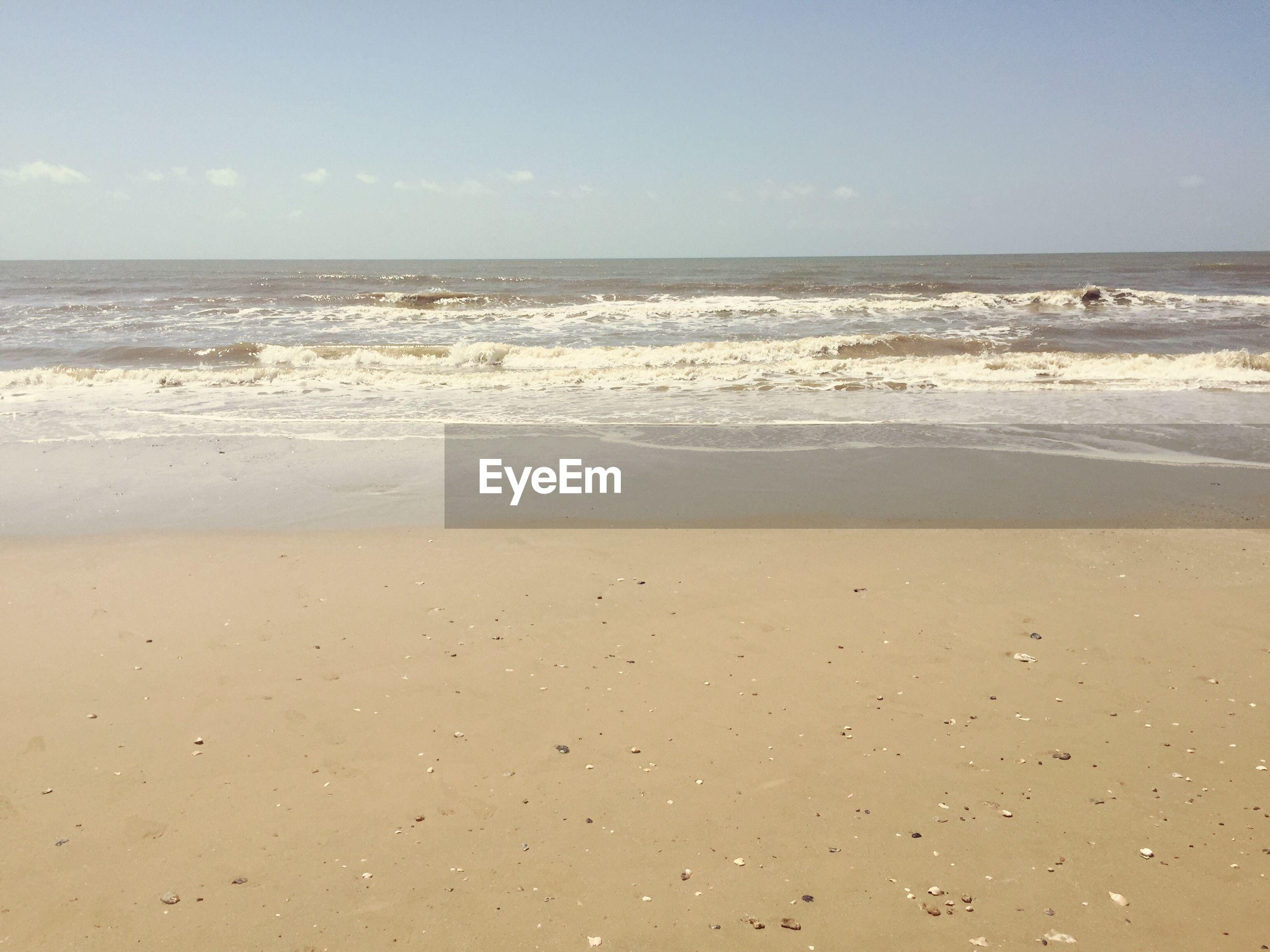 View of sandy beach against blue sky