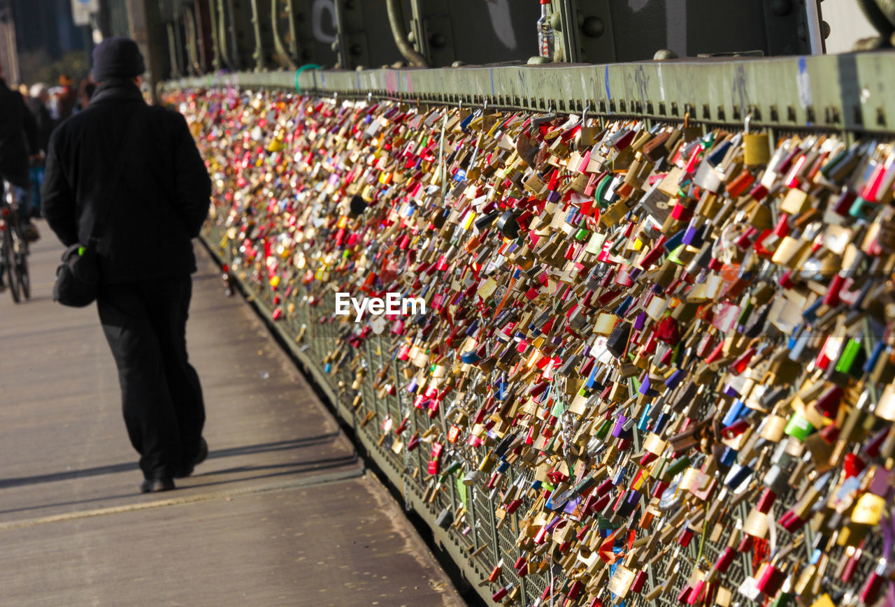Rear View Of Person Walking By Love Locks At Hohenzollern Bridge