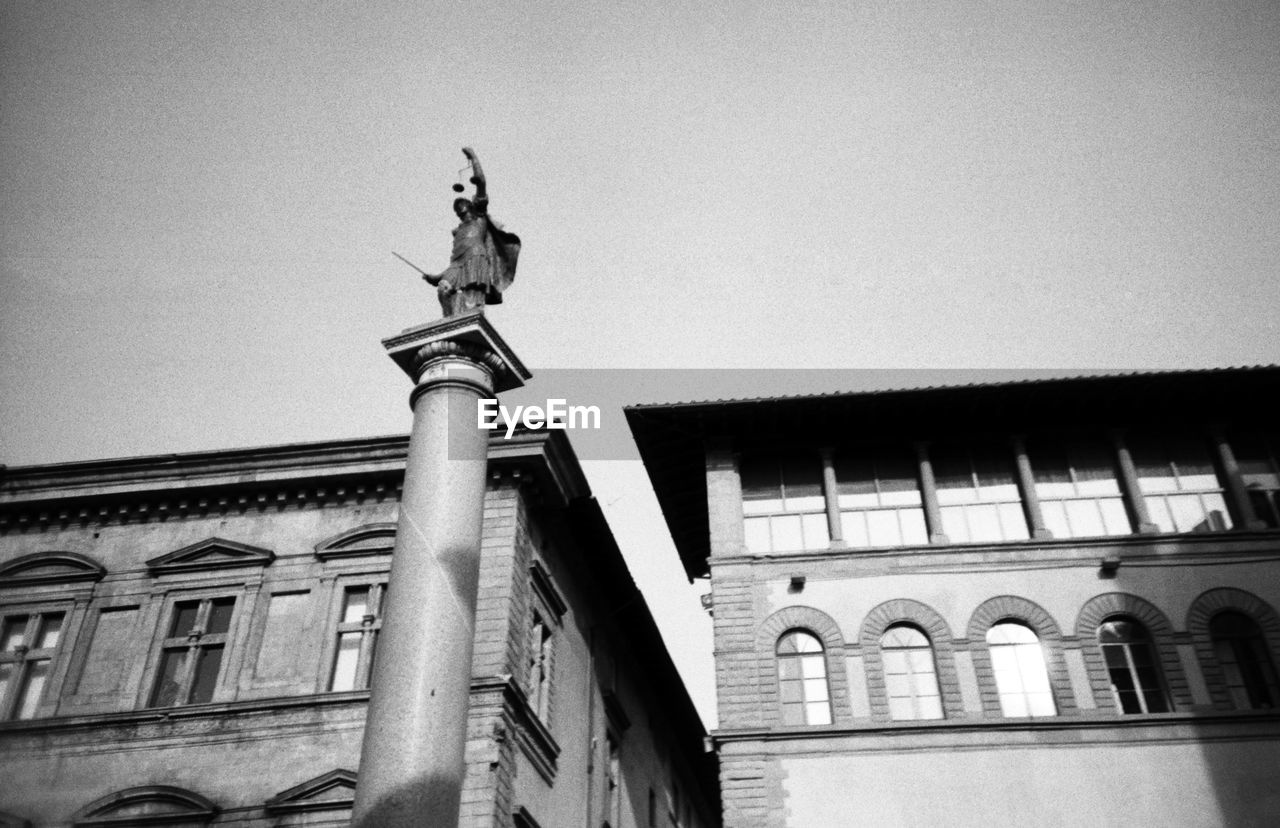 architecture, building exterior, built structure, low angle view, statue, human representation, sculpture, outdoors, day, no people, pediment, history, sky, architectural column, travel destinations, city, king - royal person, royal person