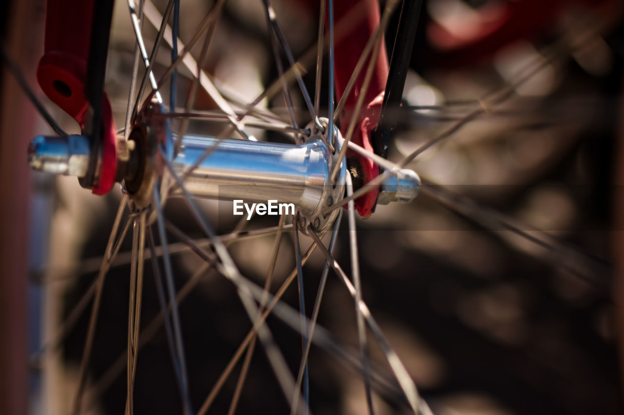 bicycle, spoke, focus on foreground, transportation, mode of transportation, no people, land vehicle, wheel, close-up, selective focus, day, stationary, outdoors, metal, vehicle part, tire, helmet, nature, pedal, safety