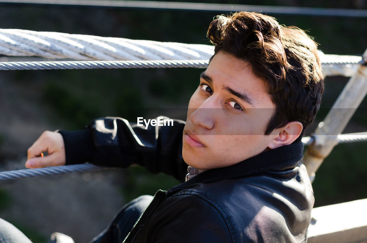Portrait Of Handsome Young Man Against Railing