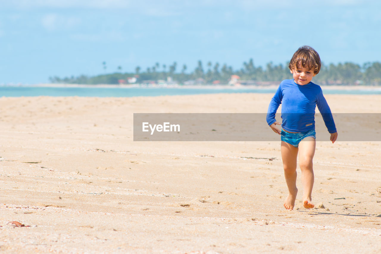 Cute Boy Walking At Beach Against Sky On Sunny Day